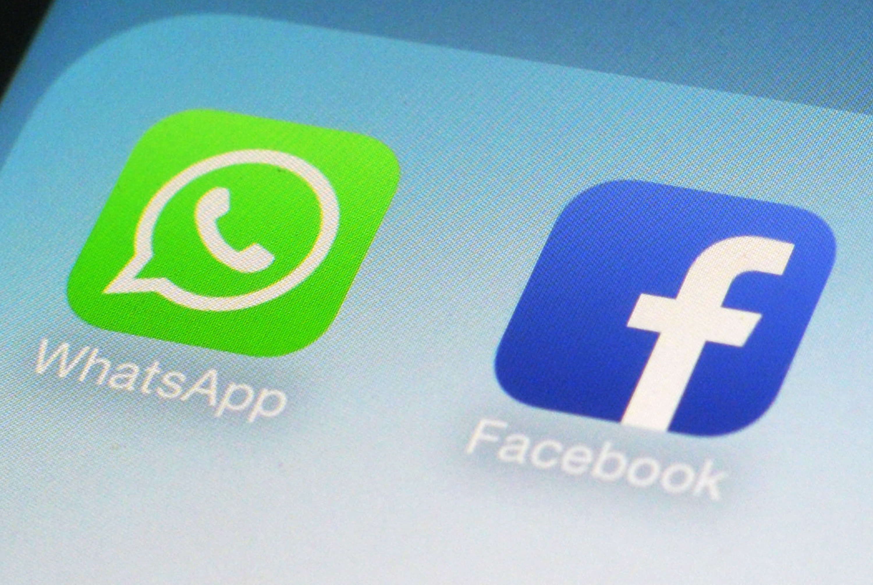 FILE - This Feb. 19, 2014, file photo, shows WhatsApp and Facebook app icons on a smartphone in New York. Global messaging service WhatsApp says it will start sharing the phone numbers of its users with Facebook, its parent company. That means WhatsApp users could soon start seeing more targeted ads on Facebook, although not on the messaging service itself. (AP Photo/Patrick Sison, File)